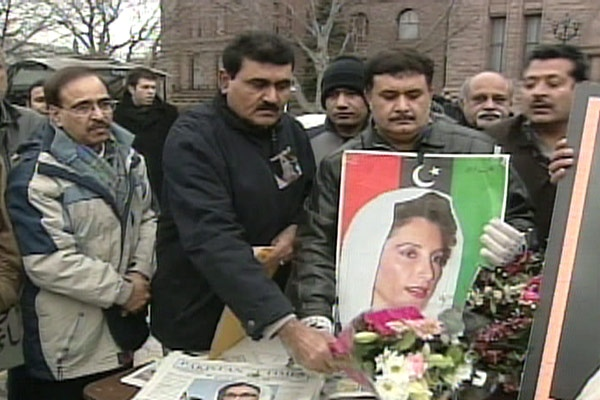 Pakistani Canadians add flowers to a memorial during a rally held at Queen's Park in Toronto on Sunday, Dec. 30, 2007.