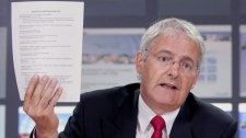 Liberal MP Marc Garneau holds up a list of individuals and organizations opposed to cuts to the long form census during a press conference in Ottawa, Wednesday July 14, 2010. (Adrian Wyld / THE CANADIAN PRESS)