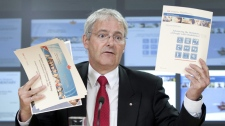 Liberal MP Marc Garneau holds up papers as he speaks about cuts to the census during a press conference in Ottawa, Wednesday July 14, 2010. (Adrian Wyld / THE CANADIAN PRESS)