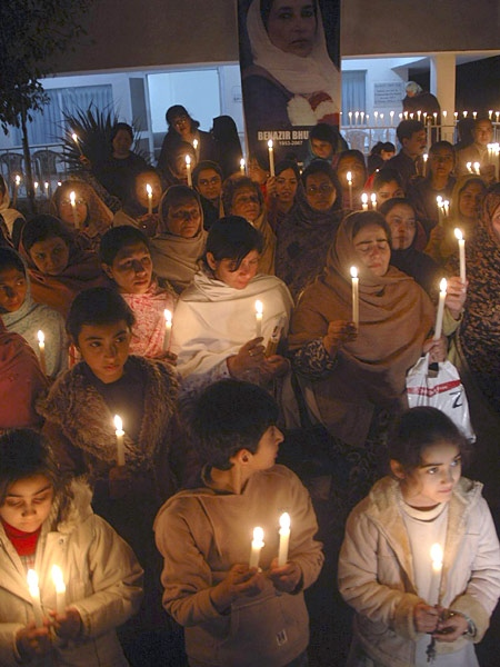 Pakistani women and children take part in a candle light ceremony at the slain Benazir Bhutto's party office in Peshawar, Pakistan on Sunday, Dec. 30, 2007. (AP / Mohammad Zubair)