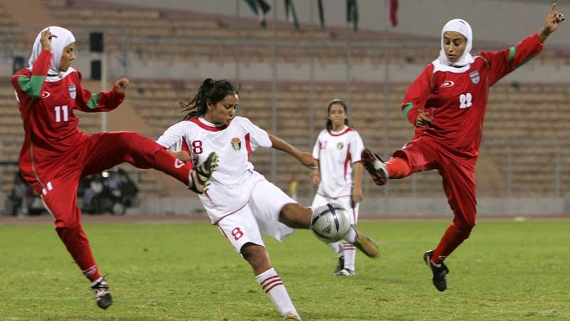 In this Oct. 1, 2005 file photo, Iranian players Saedeh Ahmadi, left, and Shihrin Nasiri, right, , battle for ball with Stephanie Al-Naber, center, of Jordan. (AP Photo/ Muhammad Al-Kisswany, File)