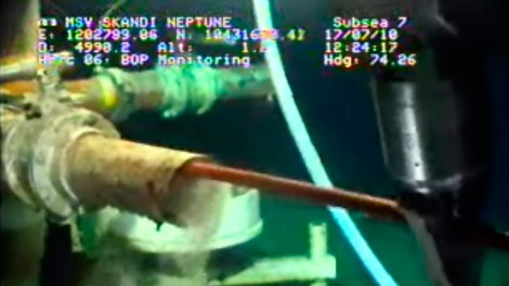 In this image taken from video provided by BP PLC at 12:24 CDT, a robotic arm uses a long wand-like object to clean out debris from a pipe at the site of the Deepwater Horizon oil spill in the Gulf of Mexico Saturday, July 17, 2010. (AP / BP PLC)