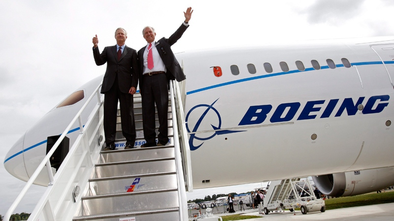 Boeing executives react as they pose with a Boeing 787 Dreamliner after it landed, for the first time outside the US, at the Farnborough International Airshow, Farnborough, England, Sunday, July 18, 2010. (AP / Sang Tan)