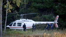 Police officers search the area around a stolen helicopter, found in Arninge, north of central Stockholm, Wednesday Sept. 23, 2009. (AP Photo/Maja Suslin)