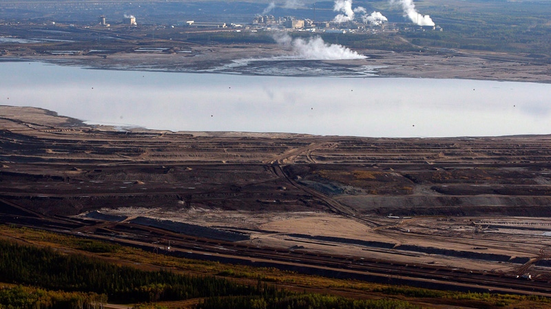 This aerial photo shows a tar sands tailings pond at a mine facility near Fort McMurray, Alta., Sept. 19, 2011. (Jeff McIntosh / THE CANADIAN PRESS)