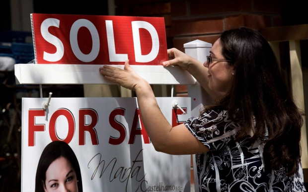A real estate agent puts up a 'sold' sign in front of a house in Toronto