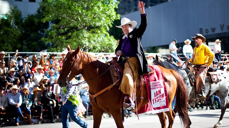 Country music legend and parade marshal Ian Tyson waves to the crowd during the Calgary Stampede parade in Calgary, Friday, July 6, 2012. (Jeff McIntosh / THE CANADIAN PRESS)