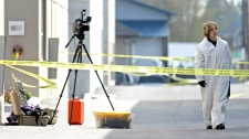 An RCMP officer investigates a crime scene in Richmond, B.C., April 15, 2009. (Darryl Dyck / THE CANADIAN PRESS)