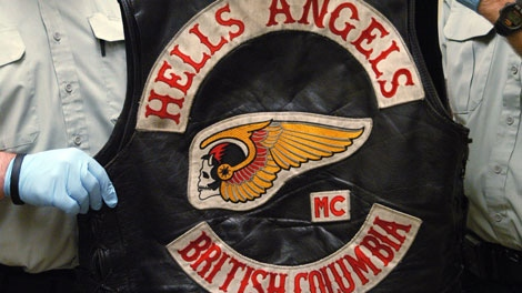 RCMP officers display a Hells Angels vest in Richmond, B.C. in this handout photo. (CP PHOTO/HO/BC RCMP)