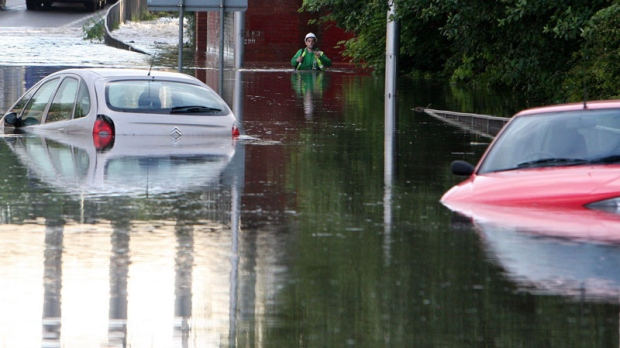 A man walks through flood water as torrential downpours cause flash floods in Jarrow, England.