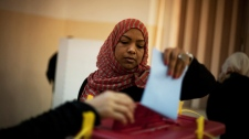 A Libyan woman votes at a polling station in the old city of Tripoli, Libya on Saturday, July 7