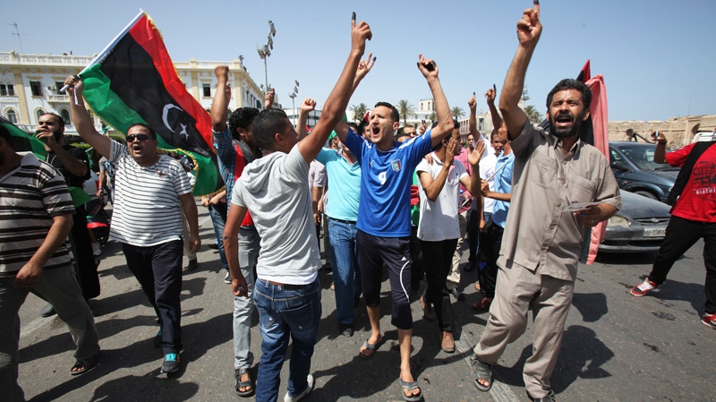 Libyans hold up their ink-marked fingers that shows they have voted as they celebrate in Martyrs' Square in Tripoli, Libya, on Saturday, July 7, 2012. (AP / Abdel Magid Al Fergany)
