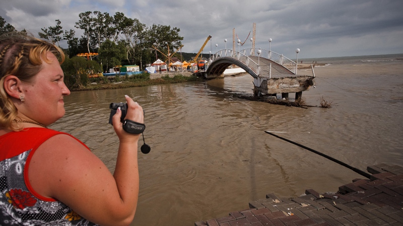 A woman takes video of the flood in the Black Sea resort of Gelendzhik, southern Russia on Saturday, July 7, 2012. (AP / Ignat Kozlov)