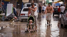 People walk in a muddy street after flooding in the Black Sea resort of Gelendzhik, southern Russia