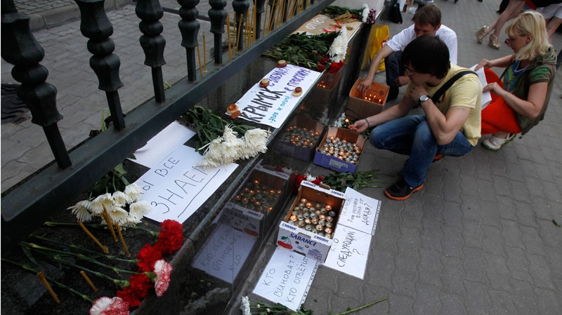 People light candles in memory of victims of the flood in Krasnodar region outside the office of the Representation of Krasnodar region in Moscow, Russia, Saturday, July 7, 2012. (AP / Misha Japaridze)