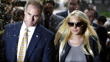 Confetti flies as Lindsay Lohan, with an unidentified man, arrives at the Beverly Hills courthouse Tuesday, July 20, 2010. (AP / Reed Saxon)