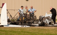 RCMP and the coroner look through the burnt wreckage of a twin engine plane crash at Marshall Field