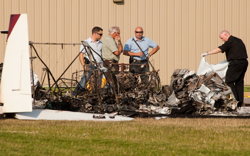 RCMP and the coroner look through the burnt wreckage of a twin engine plane crash at Marshall Field in Vernon, B.C., Saturday, July 7, 2012. (Jeff Bassett / THE CANADIAN PRESS)