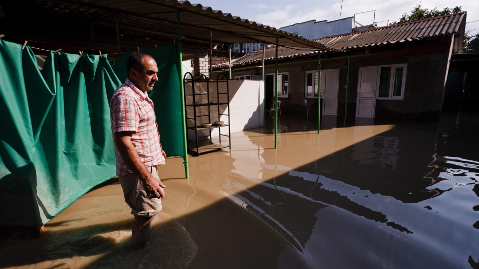 A local resident stands at a flooded house in the Black Sea resort of Gelendzhik, southern Russia, Saturday, July 7, 2012. (AP / Ignat Kozlov)