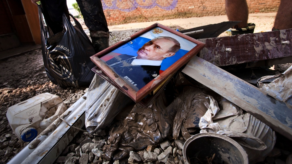 Local residents stand next to a bunch of garbage with a portrait of Russian President Vladimir Putin at a flooded house in Krimsk, about 1,200 kilometres south of Moscow, Russia, Sunday, July 8, 2012. (AP / Ignat Kozlov)