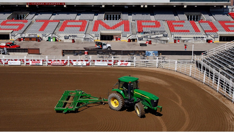 A tractor pulls a set of harrows around the rodeo arena before the competition at the Calgary Stampede in Calgary, Sunday, July 8, 2012. (Jeff McIntosh / THE CANADIAN PRESS)