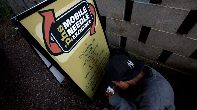 An addict uses the sign for a mobile needle exchange program to block the wind as he tries to smoke a rock of crack in an alley in Abbotsford, B.C., Thursday, July 5, 2012. A group is launching a lawsuit against the federal government over the lack of needle exchange programs in federal prisons. (Jonathan Hayward / THE CANADIAN PRESS)
