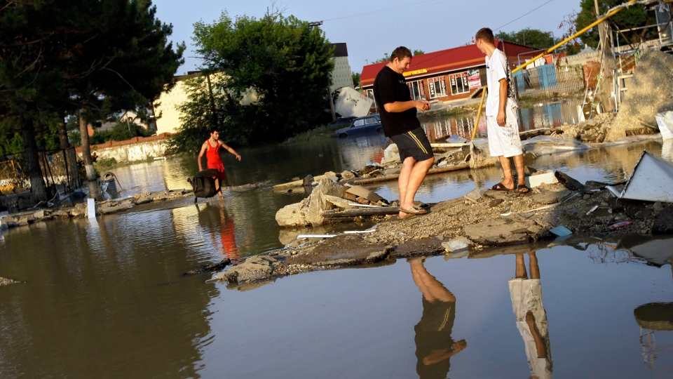 People walk along a flooded street in Krimsk, about 1,200 kilometers south of Moscow, Sunday July 8, 2012. (AP / Sergey Ponomarev)