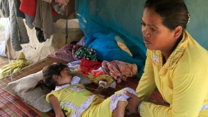 Mean Thida, 4, affected with mystery disease, sleeps beside her mother as she receives treatment via a bottle of serum, not in photo, at their home near a dump site at Sambour village, on the outskirts of Phnom Penh, Cambodia, Monday, July 9, 2012. (AP / Heng Sinith)
