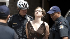 An Ontario Coalition Against Poverty activist is led away by police after being arrested following an occupation of Liberal Party offices in Toronto on Wednesday July 21, 2010. (THE CANADIAN PRESS/Chris Young)