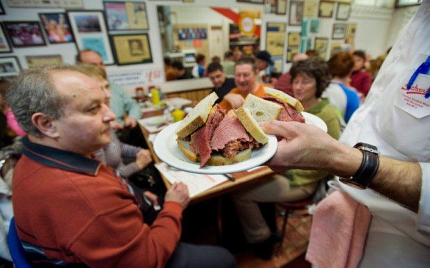 A waiter serves up smoked meat sandwiches at Schwartz's deli in Montreal