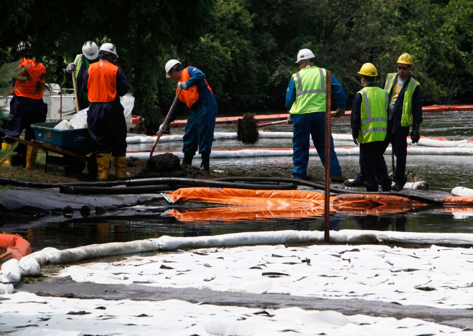 Crews clean up oil, from a ruptured pipeline, owned by Enbridge Inc, near booms and absorbent materials where Talmadge Creek meets the Kalamazoo River as in Marshall Township, Mich., July 30, 2010. (AP / Paul Sancya)