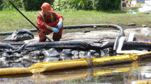 In this July 29, 2010, file photo, a worker monitors water in Talmadge Creek in Marshall Township, Mich., near the Kalamazoo River as oil from a ruptured pipeline, owned by Enbridge Inc., is attempted to be trapped by booms.(AP Photo/Paul Sancya, File)