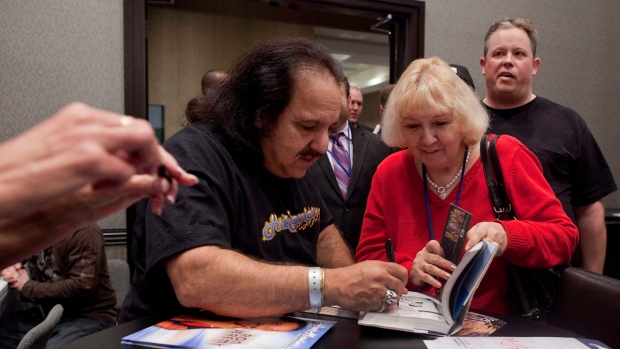 Adult film star Ron Jeremy, left, signs his book during the Adult Video Network Expo