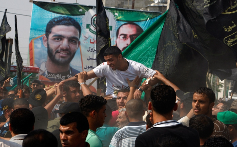 Palestinian Mahmoud Sarsak, a former player with the Palestinian national football team, is carried by supporters upon his arrival to his family's house in Rafah, southern Gaza Strip, after his release from Israeli prison, on Tuesday, July 10, 2012. (AP / Adel Hana)