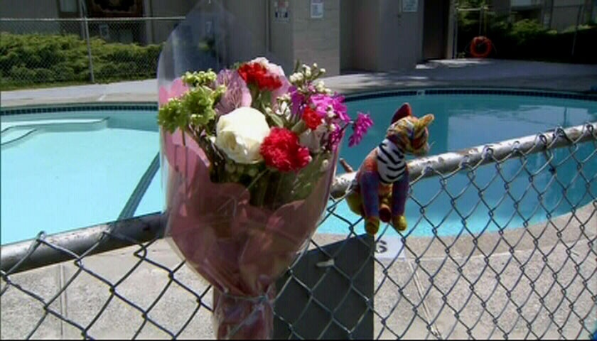 Flowers are placed at the pool where a Surrey, B.C. woman and her grandson drowned.