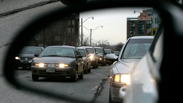 Commuters are reflected in a rearview mirror while sitting in rush hour traffic in Toronto. (J.P. Moczulski / THE CANADIAN PRESS)