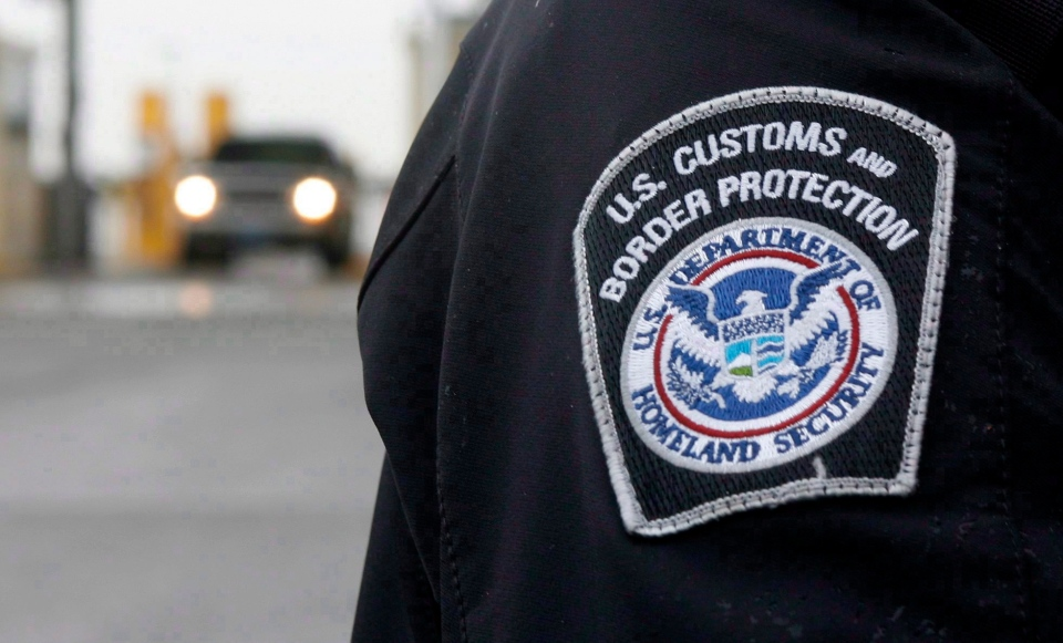 A U.S. Customs and Border Protection (CMP) officer stands near a security booth as vehicles approach in Detroit, Michigan, on June 1, 2009. (Dave Chidley / THE CANADIAN PRESS)