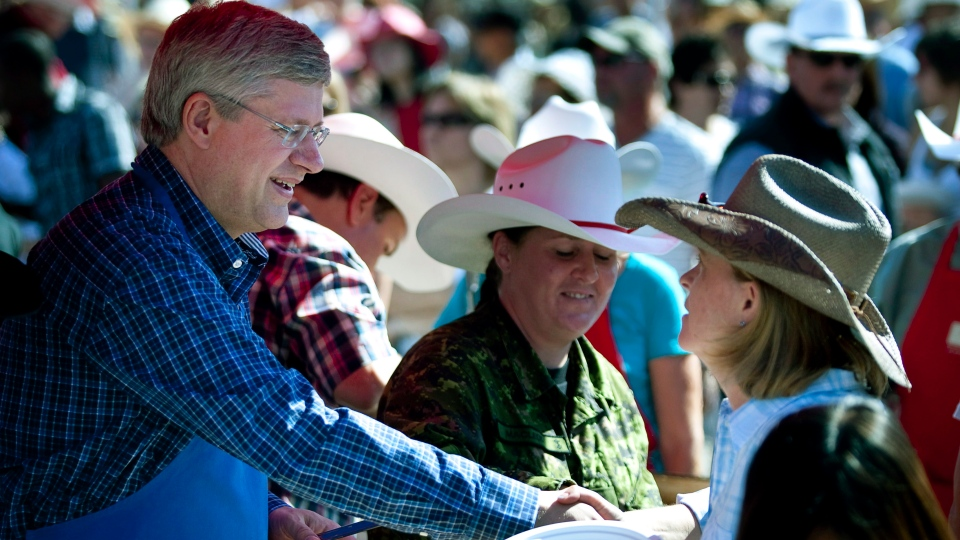 Prime Minister Stephen Harper, left, hands out pancakes while attending a Stampede breakfast in Calgary, Alta., Monday, July 9, 2012. (Jeff McIntosh / THE CANADIAN PRESS)