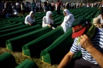 People mourn next to coffins of their relatives at the Potocari memorial complex near Srebrenica, some 160 kilometres east of Sarajevo, Bosnia and Herzegovina, Wednesday, July 11, 2012. (AP / Marko Drobnjakovic)