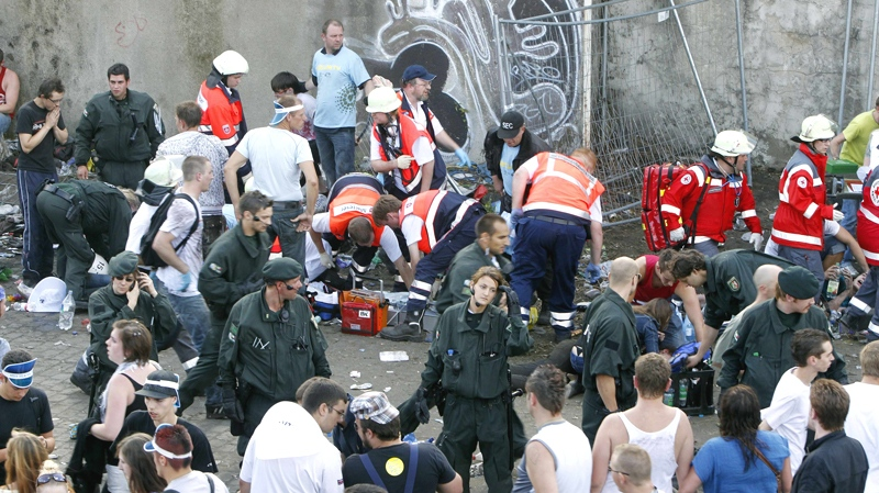 "Collapsed people get first aid after a panic on this year's techno-music festival ""Loveparade 2010"" in Duisburg, Germany, on Saturday, July 24, 2010. (AP / Hermann J. Knippertz)"