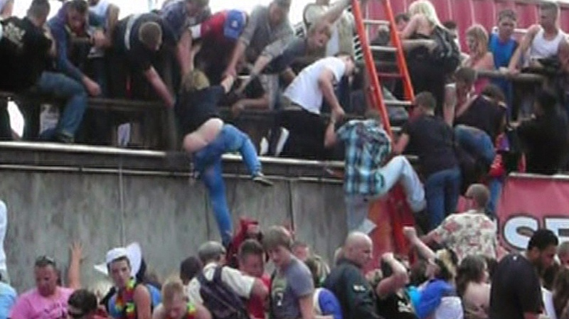"In this image taken from television people are seen trying to escape over a wall after a panic on this year's techno-music festival ""Loveparade 2010"" in Duisburg, Germany, on Saturday, July 24, 2010. (AP / WIEBOLD TV via APTN)"