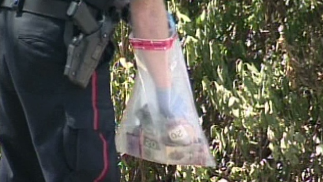 An officer collects cash found near the location of a robbery at a Scotiabank branch on Doon Village Road in Kitchener, Ont. on Thursday, July 12, 2012.