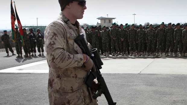 A Canadian soldier, part from the NATO-led International Security Assistance Force (ISAF), walks as Afghan soldiers stand during a graduation ceremony at a military training centre in Kabul, Afghanistan, Wednesday, March 14, 2012. (AP Photo/Musadeq Sadeq)