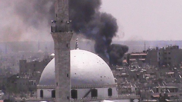 Black smoke rises from buildings near a mosque from purported forces shelling in Homs, Syria, on Wednesday, July 11, 2012. (Shaam News Network)