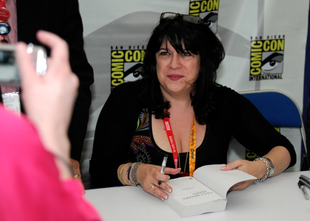 E.L. James signs a copy of her book 'Fifty Shades of Grey' during the first day of Comic-Con convention held at the San Diego Convention Center on Thursday July 12, 2012, in San Diego. (Denis Poroy / Invision)
