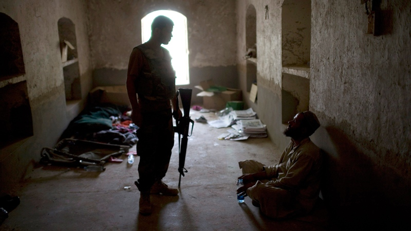 An Afghan soldier stands guard next to a villager who was detained at COP Nolen due to trace amounts of Ammonium Nitrate found on his fingers, the key component used in manufacturing IEDs, in the volatile Arghandab Valley, Kandahar, Afghanistan, Sunday, July 25, 2010. (AP / Rodrigo Abd)