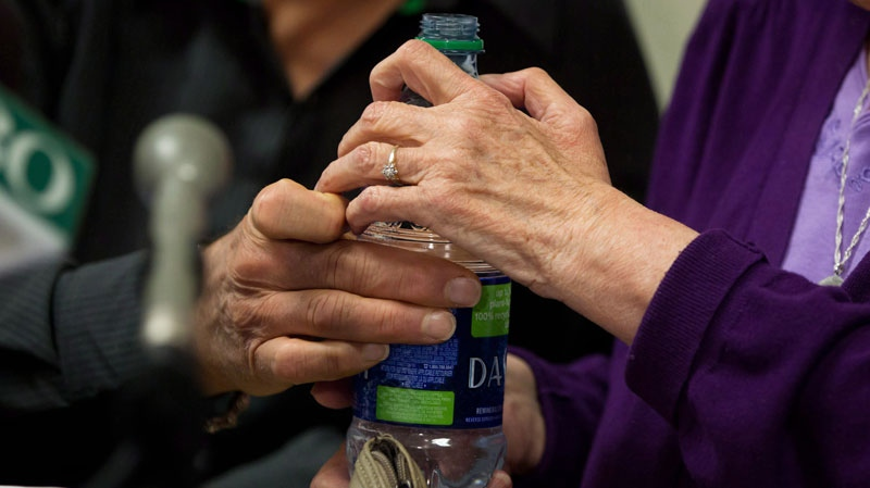 Gloria Taylor, right, who suffers from Lou Gehrig's disease, is assisted in picking up a bottle of water by Hollis Johnson during a news conference in Vancouver, B.C., on Monday, June 18, 2012. (Darryl Dyck / THE CANADIAN PRESS)