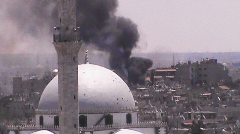 In this citizen journalism image provided by Shaam News Network SNN, taken on Wednesday, July 11, 2012, black smoke rises from buildings near a mosque from purported forces shelling in Homs, Syria. (AP Photo/Shaam News Network, SNN)