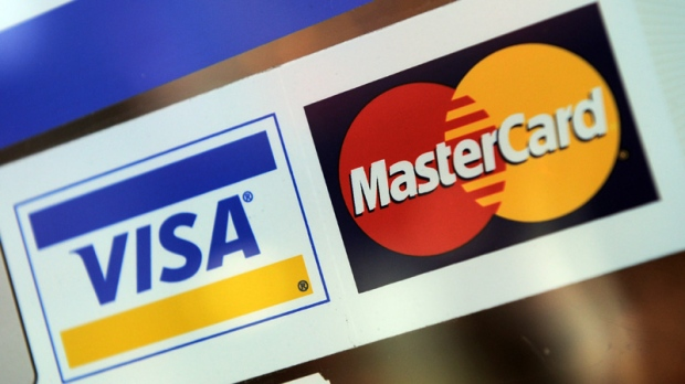 In ths May 8, 2012 photo, Visa and MasterCard signs are displayed on a store window in Ottawa.