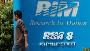 An employee walks past the Research In Motion company logo in front of one of their many buildings, in Waterloo, Ontario on Friday, June 29, 2012. (Dave Chidley / THE CANADIAN PRESS)